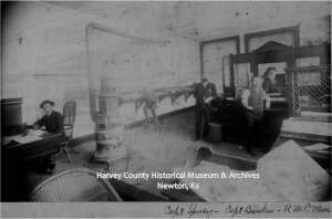 Office of Judge RWP Muse and Capt. Spivey, Newton 1872.  Spivey is sitting at the desk, Judge Muse is behind the counter and the man in front of the counter is identified as Capt. Bunker.  Fourth man is undientified.